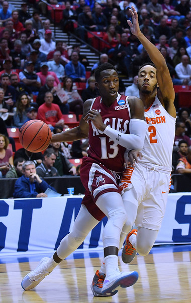 SAN DIEGO, CA - MARCH 16:  Sidy N'Dir #13 of the New Mexico State Aggies drives against Marcquise Reed #2 of the Clemson Tigers during a first round game of the Men's NCAA Basketball Tournament at Viejas Arena in San Diego, California. Clemson won 79-68.  (Photo by Sam Wasson)