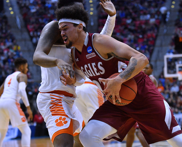 SAN DIEGO, CA - MARCH 16:  Eli Chuha #22 of the New Mexico State Aggies drives to the basket against Elijah Thomas #14 of the Clemson Tigers during a first round game of the Men's NCAA Basketball Tournament at Viejas Arena in San Diego, California. Clemson won 79-68.  (Photo by Sam Wasson)