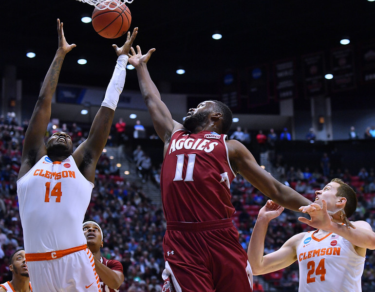 SAN DIEGO, CA - MARCH 16:  Johnathon Wilkins #11 of the New Mexico State Aggies battles Elijah Thomas #14 of the Clemson Tigers for a rebound during a first round game of the Men's NCAA Basketball Tournament at Viejas Arena in San Diego, California. Clemson won 79-68.  (Photo by Sam Wasson)
