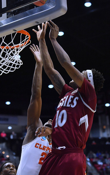 SAN DIEGO, CA - MARCH 16:  Jemerrio Jones #10 of the New Mexico State Aggies gets a layup against Aamir Simms #25 of the Clemson Tigers during a first round game of the Men's NCAA Basketball Tournament at Viejas Arena in San Diego, California. Clemson won 79-68.  (Photo by Sam Wasson)