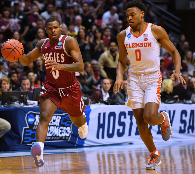 SAN DIEGO, CA - MARCH 16:  Keyon Jones #0 of the New Mexico State Aggies brings the ball up the court against Clyde Trapp #0 of the Clemson Tigers during a first round game of the Men's NCAA Basketball Tournament at Viejas Arena in San Diego, California. Clemson won 79-68.  (Photo by Sam Wasson)