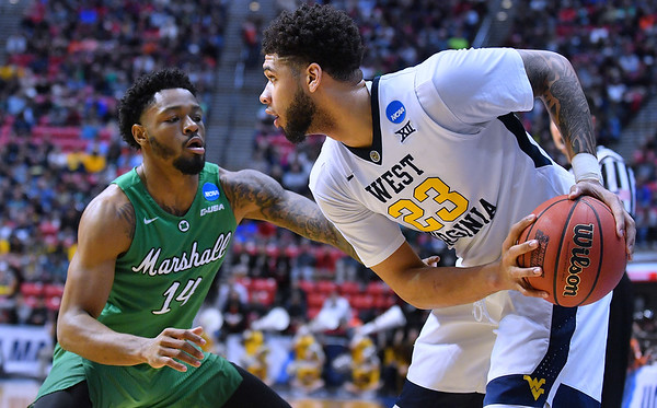 SAN DIEGO, CA - MARCH 18:  West Virginia Mountaineers forward Esa Ahmad (23) looks to drive against Marshall Thundering Herd guard C.J. Burks (14) during a second round game of the Men's NCAA Basketball Tournament at Viejas Arena in San Diego, California.  (Photo by Sam Wasson)