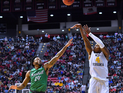 SAN DIEGO, CA - MARCH 18:  West Virginia Mountaineers guard Daxter Miles Jr. (4) shoots against Marshall Thundering Herd guard C.J. Burks (14) during a second round game of the Men's NCAA Basketball Tournament at Viejas Arena in San Diego, California.  (Photo by Sam Wasson)