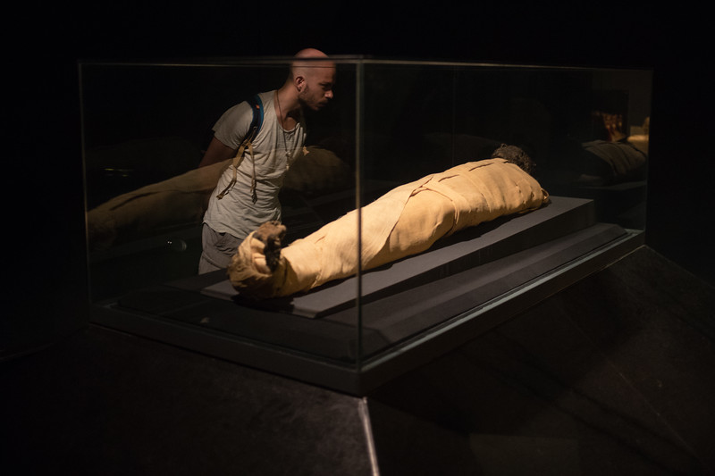A tourist examines a mummy in the Luxor Museum in Upper Egypt.