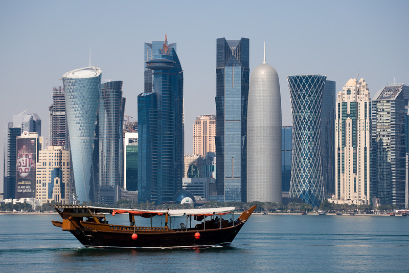 A traditional dhow boat sails past the skyscrapers of West Bay in Doha, Qatar.