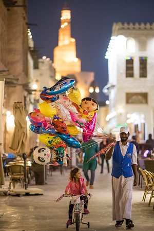 A child bicycles past a ballon vendor at the Souq Waqif market area of Doha, Qatar.