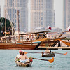 Men in traditional costume paddle a small boat in the Katara Cultural Complex area of Doha, Qatar.