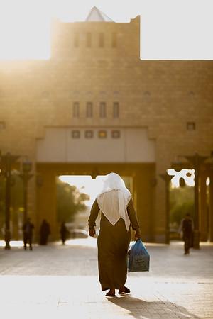 A local man in traditional clothing walks across Al Safa Square in Riyadh, Saudi Arabia.