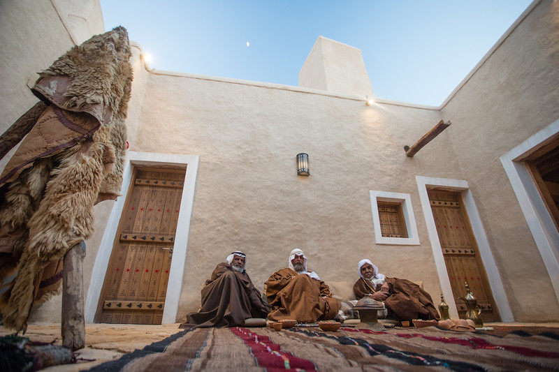 Local men in traditional costume sit in a courtyard in the Diriyah neighborhood of Riyadh, Saudi Arabia.