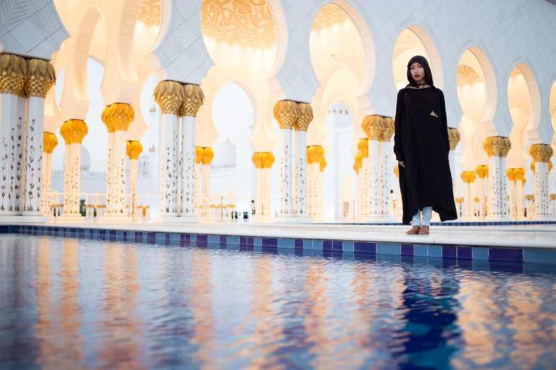 A tourist poses near the entrance of the Sheikh Zayed Grand Mosque in Abu Dhabi, UAE.