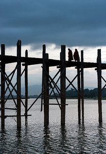 Buddhist monks walk the U Bein Bridge across the Taungthaman Lake in Amarapura near Mandalay, Burma (Myanmar)
