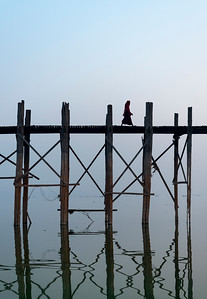 Buddhist monk crosses the U Bein Bridge - the longest teakwood footbridge in the world in Amarapura near Mandalay, Burma (Myanmar)