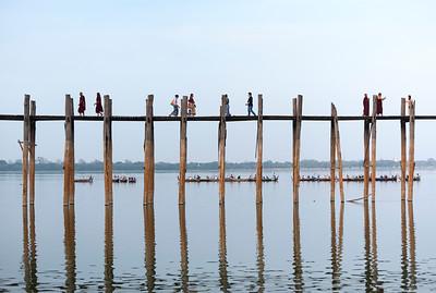 People cross U Bein Bridge - the longest teakwood footbridge in the world, Amarapura near Mandalay, Burma (Myanmar)