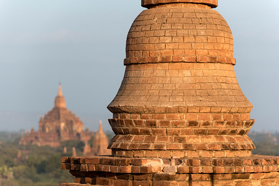 Small stupa atop the terrace of Pyathada Paya with Htilominlo Temple in the background, Bagan, Burma - Myanmar