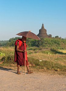 Buddhist monk with umbrella, Mrauk U, Burma