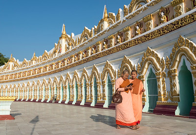 Buddhist monks in front of the curved chamber of Umin Thounzeh (U Min Thonze) Pagoda in Sagaing near Mandalay, Myanmar (Burma)