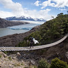 Crossing a hanging bridge on the Torres del Paine trek, with Glacier Grey in the background.