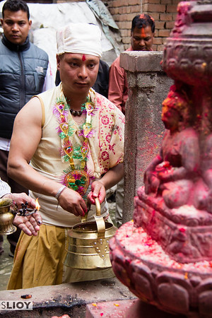 Making a devotional offering at a small Hindu shrine before the start of the Sunder Jatra ritual.