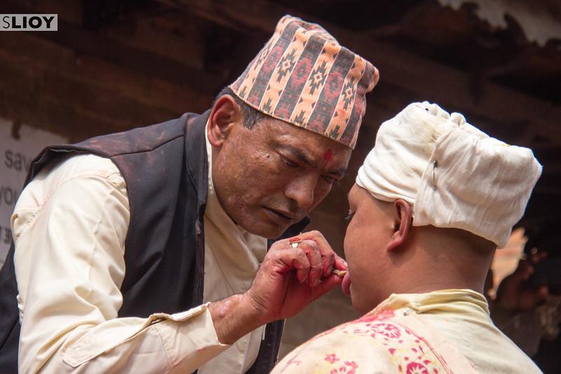Village elders prepare the volunteer to have his tongue pierced during the Sunder Jatra ritual, as part of the large Bisket Jatra festival in Nepal.