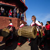 A group of costumed musicians circle around the central Yoshin Pole in the lower town area of Bhaktapur.