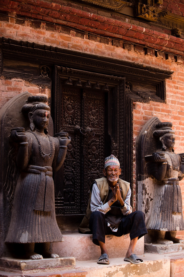 Old man posing on the steps of Durbar Square in Bhaktapur, Kathmandu Valley, Nepal.