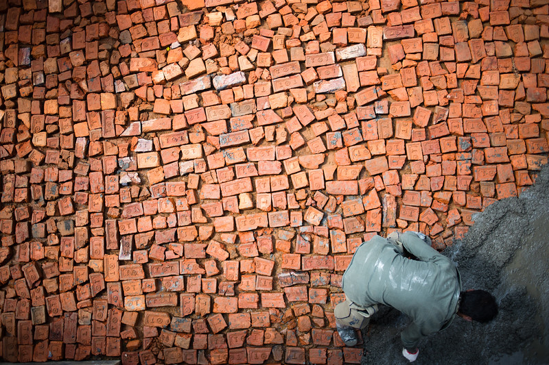 A local man lays bricks in a village near Bhaktapur in Nepal's Kathmandu Valley.