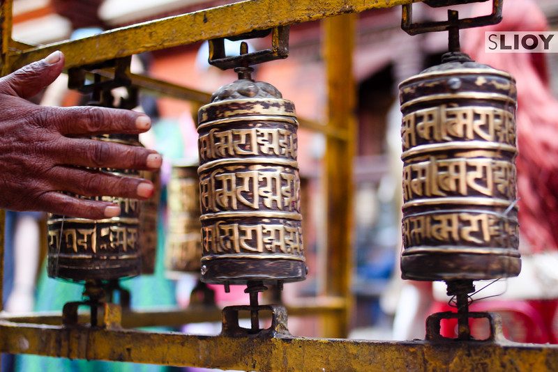 Spinning a prayer wheel at a Patan Buddhist temple.