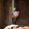 Small girl hiding from strangers on the trail near Nagarkot in the Kathmandu Valley of Nepal.