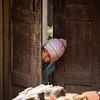 Small girl hiding from strangers on the trail near Nagarkot in the Kathmandu Valley of Nepal.