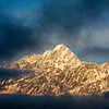Clouds cover snowy mountain peaks at sunset along the Tamang Heritage Trail in Nepal.