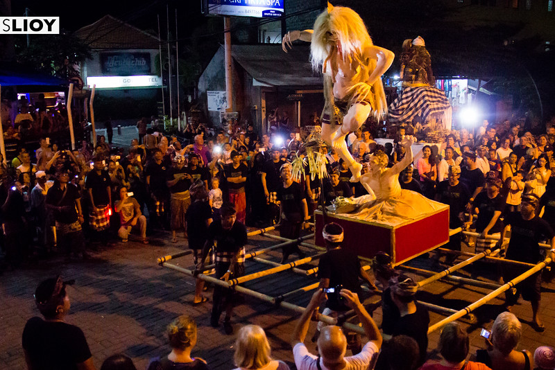 Crowds of tourists and locals watching the Tawur Keanga procession before Nyepi Day of Silence in Bali.