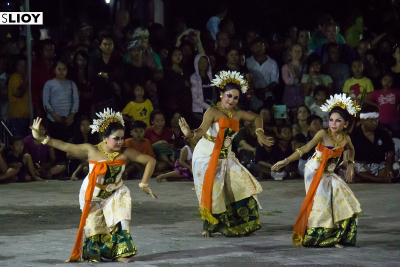 Balinese girls dancing at the end of the Tawur Kesanga procession before Nyepi Day of Silence in Bali.