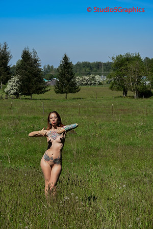 Theresa nude outdoors in a field