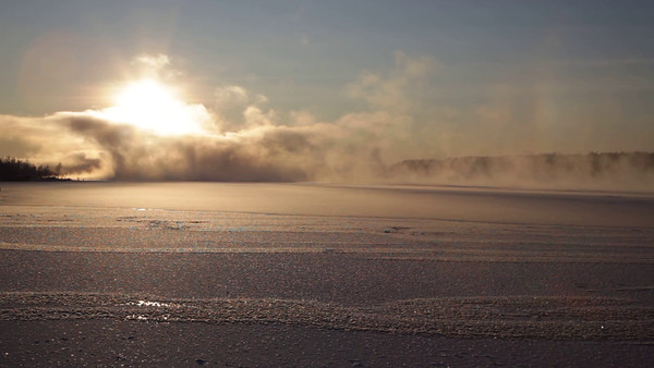 Clouds of steam rise over a freezing river illuminated by low winter sun
