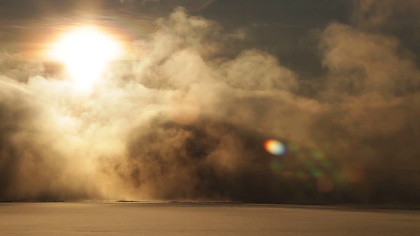 Clouds of steam rise over a freezing river illuminated by the sun