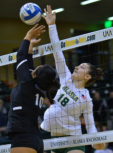 ANCHORAGE, AK - SEPTEMBER 9:  Vanessa Hayes #18 of the Alaska Anchorage Seawolves hits an over pass against Diana Maile #10 of the Cal State San Bernardino Coyotes in a match between the Alaska Anchorage Seawolves and the Cal State San Bernardino Coyotes at the Alaska Airlines Center in Anchorage, Alaska. The Coyotes won 3-2.  (Photo by Sam Wasson)