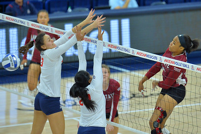 September 18, 2015: Sasha-Lee Thomas sets a ball past the Arizona blockers in a match between New Mexico State and No. 16 Arizona at McKale Memorial Center in Tucson, Ariz.