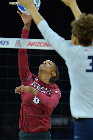 TUCSON, AZ - SEPTEMBER 15:  Tatyana Battle #6 of the New Mexico State Aggies takes a swing against Jade Turner #33 of the Arizona Wildcats in a match between the New Mexico State Aggies and the Arizona Wildcats at the McKale Center in Tucson, Arizona. The Wildcats won 3-2.  (Photo by Sam Wasson)