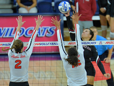 TUCSON, AZ - SEPTEMBER 15:  Jordan Abalos #3 of the New Mexico State Aggies tips a ball over the block attempt of Jaelyn Keene #2 and Lexi Varga #16 of the Illinois State Redbirds in a match between the New Mexico State Aggies and the Illinois State Redbirds at the McKale Center in Tucson, Arizona. The Redbirds won 3-0.  (Photo by Sam Wasson)