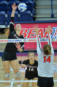 TUCSON, AZ - SEPTEMBER 15:  Kassandra Tohm #14 of the New Mexico State Aggies takes a swing against Lexi Wallen #14 of the Illinois State Redbirds in a match between the New Mexico State Aggies and the Illinois State Redbirds at the McKale Center in Tucson, Arizona. The Redbirds won 3-0.  (Photo by Sam Wasson)