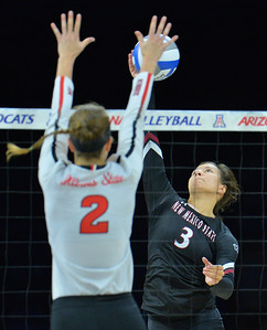 TUCSON, AZ - SEPTEMBER 15:  Jordan Abalos #3 of the New Mexico State Aggies takes a swing against Jaelyn Keene #2 of the Illinois State Redbirds in a match between the New Mexico State Aggies and the Illinois State Redbirds at the McKale Center in Tucson, Arizona. The Redbirds won 3-0.  (Photo by Sam Wasson)