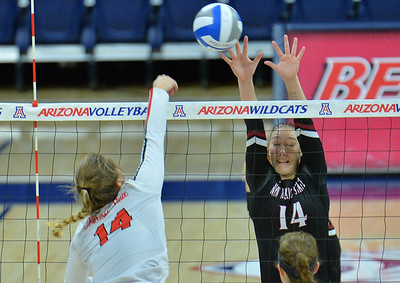 TUCSON, AZ - SEPTEMBER 15:  Kassandra Tohm #14 of the New Mexico State Aggies goes up for a block attempt against Lexi Wallen #14 of the Illinois State Redbirds in a match between the New Mexico State Aggies and the Illinois State Redbirds at the McKale Center in Tucson, Arizona. The Redbirds won 3-0.  (Photo by Sam Wasson)