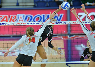 TUCSON, AZ - SEPTEMBER 15:  Brielle Sterns #13 of the New Mexico State Aggies hits a ball between the block attempt of Lexi Wallen #14 and Jaelyn Keene #2 of the Illinois State Redbirds in a match between the New Mexico State Aggies and the Illinois State Redbirds at the McKale Center in Tucson, Arizona. The Redbirds won 3-0.  (Photo by Sam Wasson)