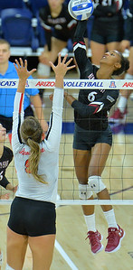 TUCSON, AZ - SEPTEMBER 15:  Tatyana Battle #6 of the New Mexico State Aggies takes a swing against Stef Jankiewicz #9 of the Illinois State Redbirds in a match between the New Mexico State Aggies and the Illinois State Redbirds at the McKale Center in Tucson, Arizona. The Redbirds won 3-0.  (Photo by Sam Wasson)