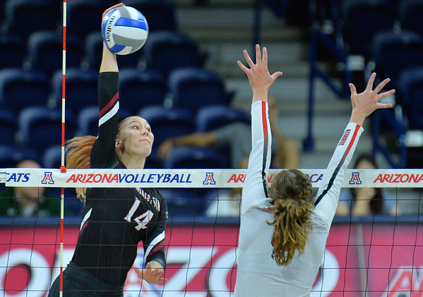 TUCSON, AZ - SEPTEMBER 15:  Kassandra Tohm #14 of the New Mexico State Aggies takes a swing against Stef Jankiewicz #9 of the Illinois State Redbirds in a match between the New Mexico State Aggies and the Illinois State Redbirds at the McKale Center in Tucson, Arizona. The Redbirds won 3-0.  (Photo by Sam Wasson)