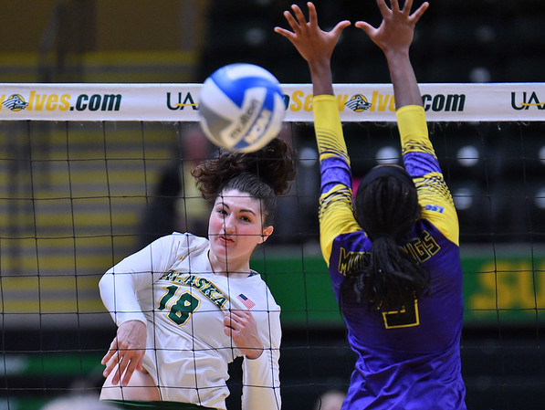 ANCHORAGE, AK - AUGUST 23:  Vanessa Boyer #18 of the Alaska Anchorage Seawolves takes a swing against Bria Augustine #5 of the Western New Mexico Mustangs during their match at the Alaska Airlines Center on August 23, 2018 in Anchorage, Alaska. The Seawolves won 3-0.  (Photo by Sam Wasson)