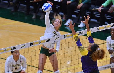 ANCHORAGE, AK - AUGUST 23:  Eve Stephens #16 of the Alaska Anchorage Seawolves takes a swing against Deyzha Samuelu #18 of the Western New Mexico Mustangs during their match at the Alaska Airlines Center on August 23, 2018 in Anchorage, Alaska. The Seawolves won 3-0.  (Photo by Sam Wasson)