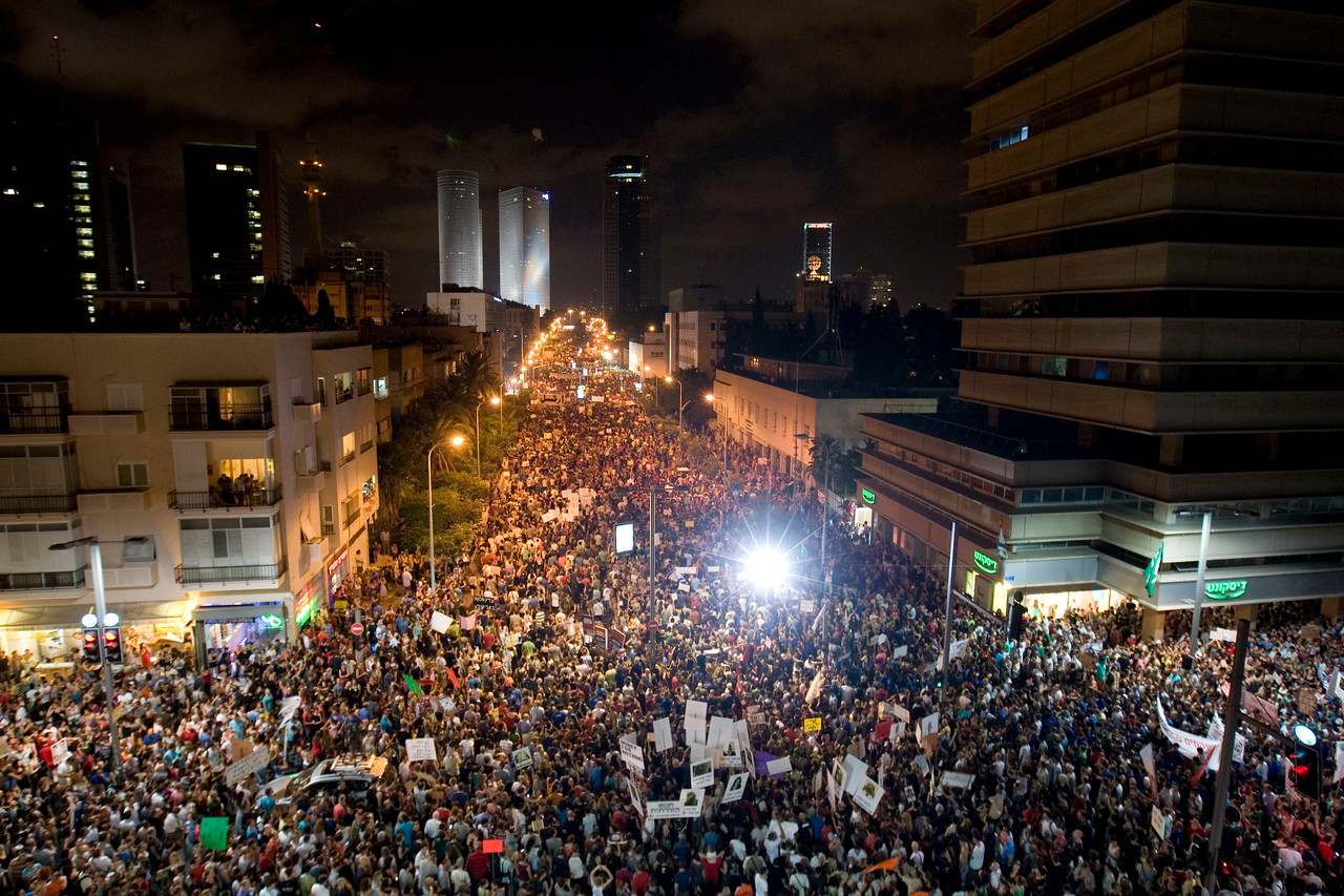 """Thousands of Israelis march during a protest against the rising cost of living in Israel, in central Tel Aviv , Israel, Saturday, Aug. 6, 2011. Angry over the ever increasing cost of living, Israelis poured en masse into the streets of major cities Saturday night in a big show of force by the protest movement that is sweeping the country and proving to be a real challenge to Prime Minister Benjamin Netanyahu's government. Thousands of mostly middle class Israelis marched through the streets in central Tel Aviv waving flags, beating drums and chanting: """"Social justice for the people.""""(AP Photo/Ariel Schalit)"""
