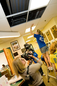 A news crew from TV3 videotapes Westfield State University student volunteers install ceiling panels at the Boys & Girls Club as part of WSU's HOOT Day (Helping Out Our Town) Tuesday Sept. 6th 2011