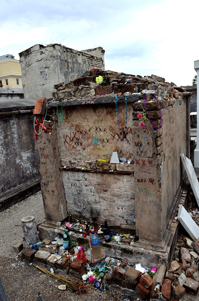 This is the tomb of Dr. John, a famous voodoo priest.  All of the items placed in front of the tomb are offerings people give to the late priest.